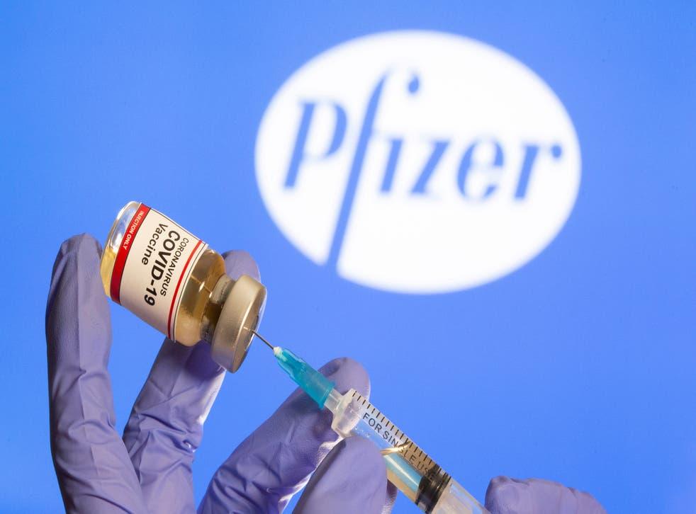 """<p>Una mujer sostiene una pequeña botella etiquetada con una etiqueta adhesiva de """"Vacuna contra el coronavirus COVID-19"""" y una jeringa médica frente al logotipo de Pfizer que se muestra el 30 de octubre de 2020.</p>"""