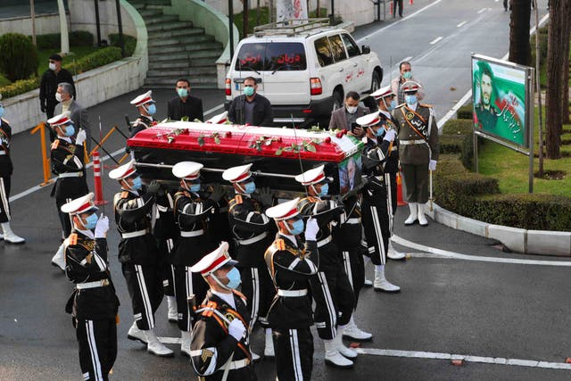 <p>Iranian military personnel carrying the flag-draped coffin of nuclear scientist Mohsen Fakhrizadeh</p>