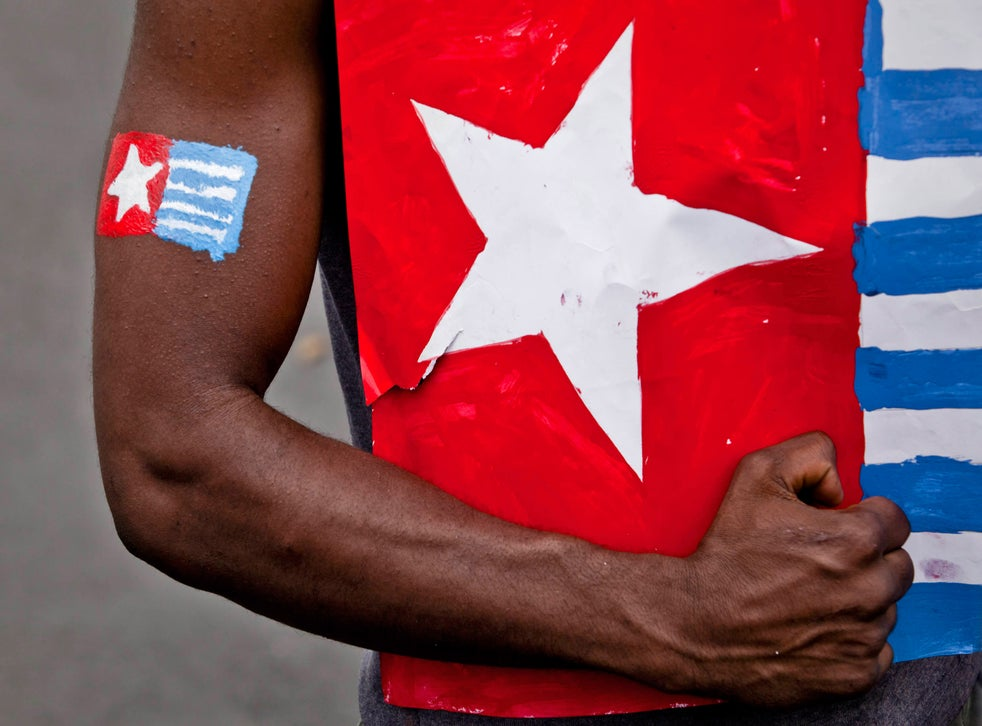 A protester from the Papuan Students Alliance holds the Morning Star flag during a protest on August 15, 2013 in Yogyakarta, Indonesia. Raising the Morning Star flag is illegal in West Papua.