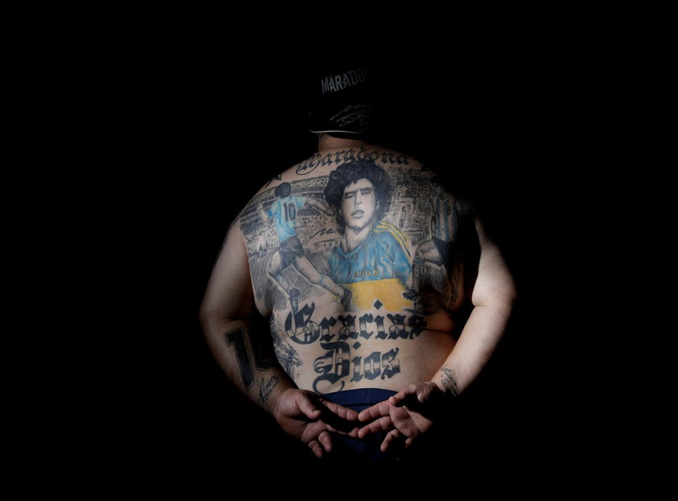 Guillermo Rodriguez, a devoted Diego Maradona fan, shows his tattoos at his pizza shop in Buenos Aires