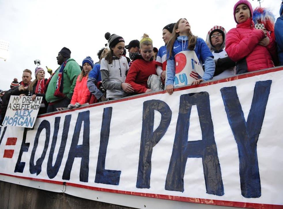 ARCHIVO - Esta foto de archivo de 2016 muestra a un grupo de aficionados detrás de un cartel que exige paga equitativa para las integrantes de la selección de fútbol femenino de Estados Unidos, durante un partido amistoso ante Colombia en East Hartford, Connecticut.