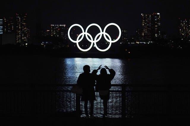 Una pareja observan los anillos olímpicos flotando en el distrito de Odaiba de Tokio, el martes 1 de diciembre de 2020.