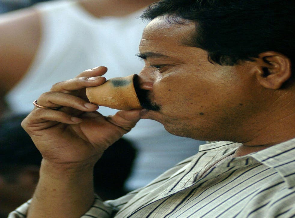 <p>File: An Indian man drinks tea from an earthenware cup</p>