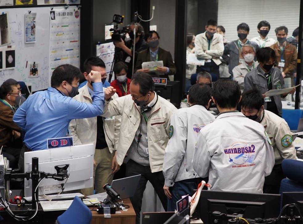 Miembros del equipo celebran el éxito de una maniobra de la sonda espacial japonesa Hayabusa2, en el control de la misión, en el Campus Sagamihara de JAXA en Sagamihara, cerca de Tokio, el 5 de diciembre de 2020.