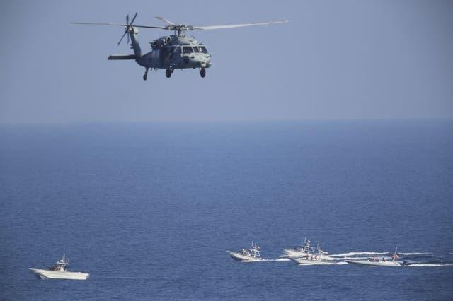 En esta foto de archivo del 21 de diciembre de 2018, un helicóptero estadounidense MH-60 Seahawk sobrevuela buques patrulla de la Guardia Nacional de Irán en el Estrecho de Hormuz.