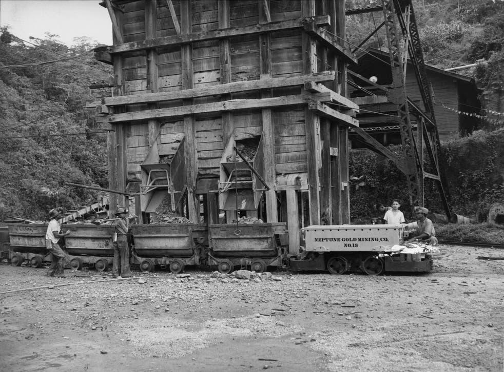 ARCHIVO- alrededor de 1955: En la mina de oro Bonanza en Nicaragua, las rocas se deslizan por toboganes desde el pozo de mineral en una fila de carros.