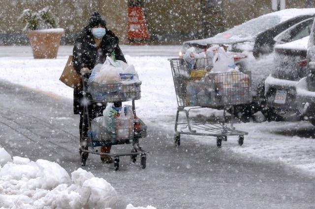 Una persona transporta comestibles en un carrito bajo una fuerte nevada en un estacionamiento en Marlborough, Massachusetts, el sábado 5 de diciembre de 2020.