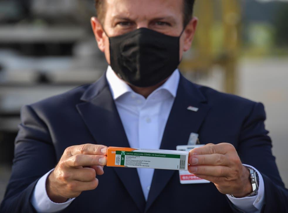 Joao Doria holds a package of the CoronaVac vaccine