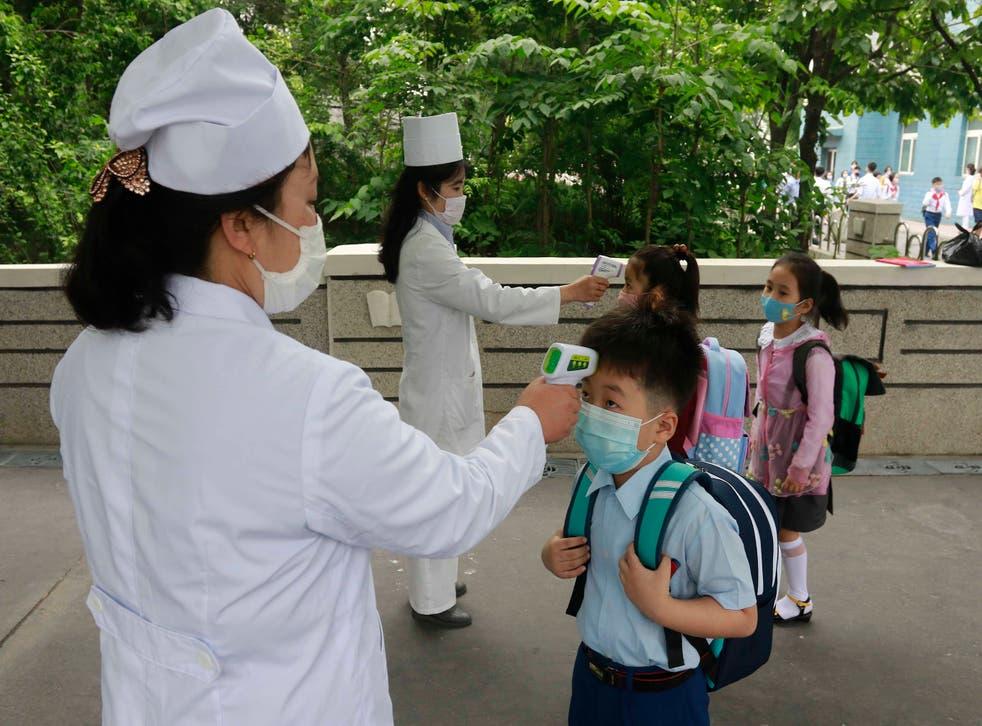 <p>Enfermeras le toman la temperatura a los alumnos en una escuela en Pyongyang, la capital de Norcorea, el 3 de junio del 2020. &nbsp;</p>
