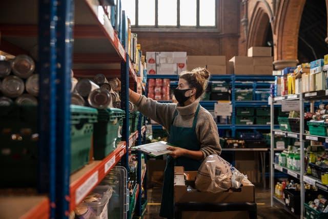 El personal y los voluntarios empacan y preparan paquetes de alimentos en el almacén y centro de distribución del sur de Londres en la iglesia de St Margaret.