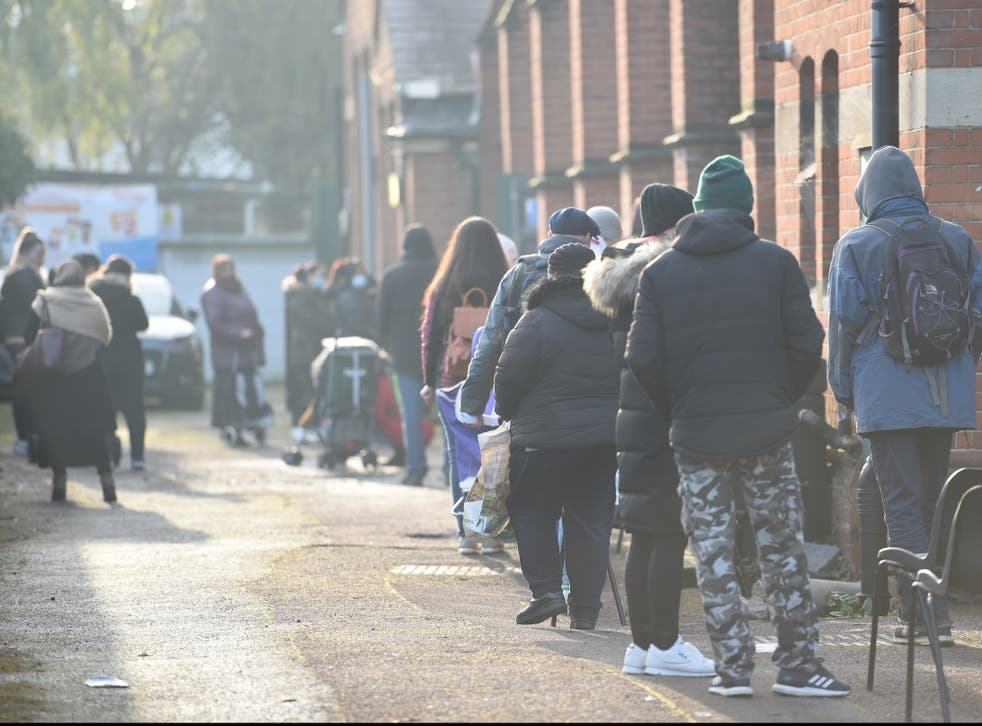 <p>Service users queue at Green Lanes food bank in north London</p>