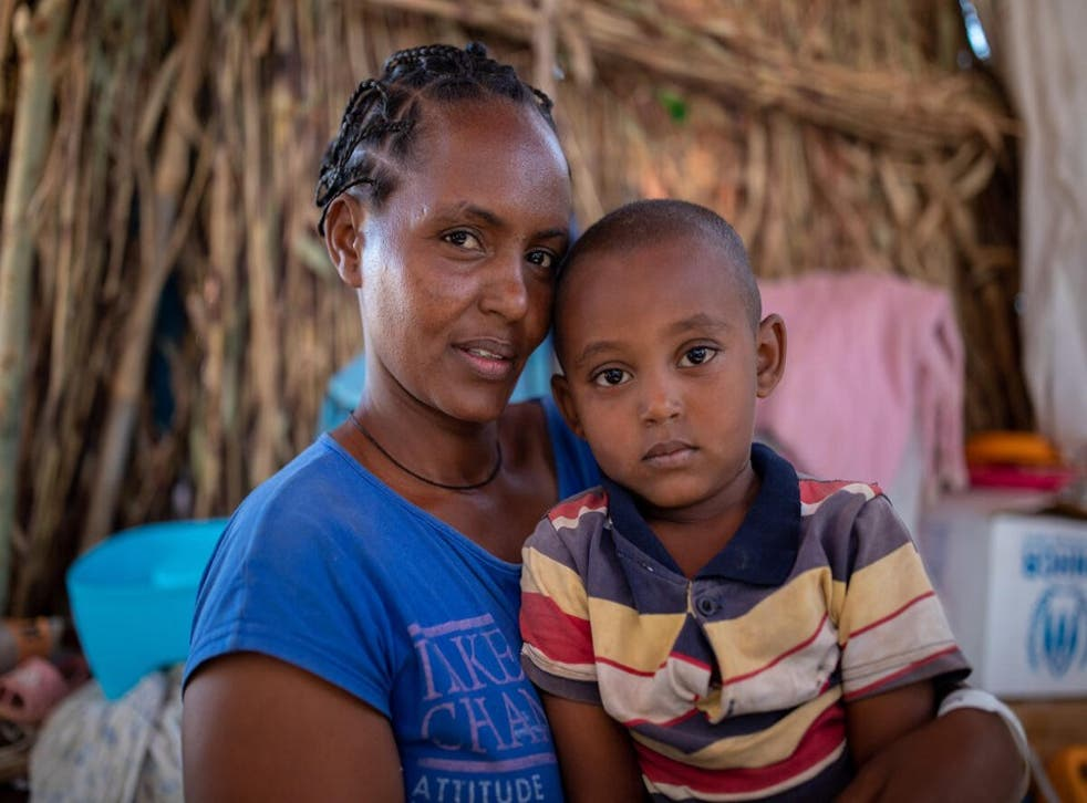 A woman with her son aged four, in UM Rakuba refugee camp in Sudan—they have received a monthly ration from WFP, including sorghum, oil, salt and millet