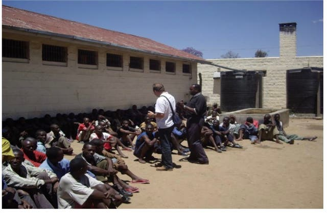 <p>Rev Paul Cowley MBE speaking to men in a high security prison in Kenya</p>
