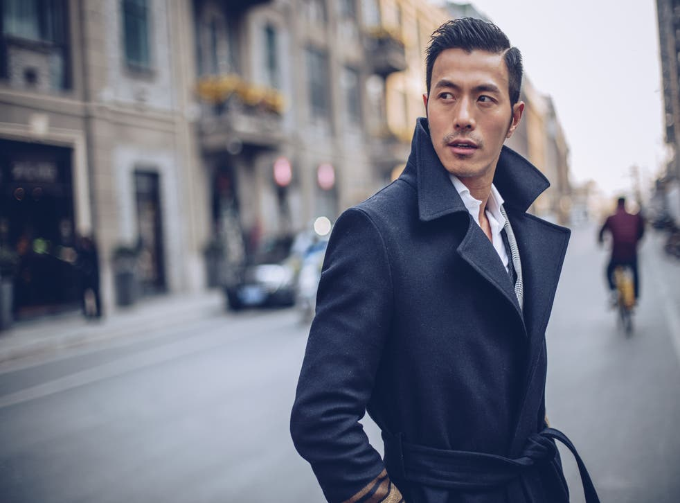 <p>Stylish man in a coat, standing on the street downtown.</p>