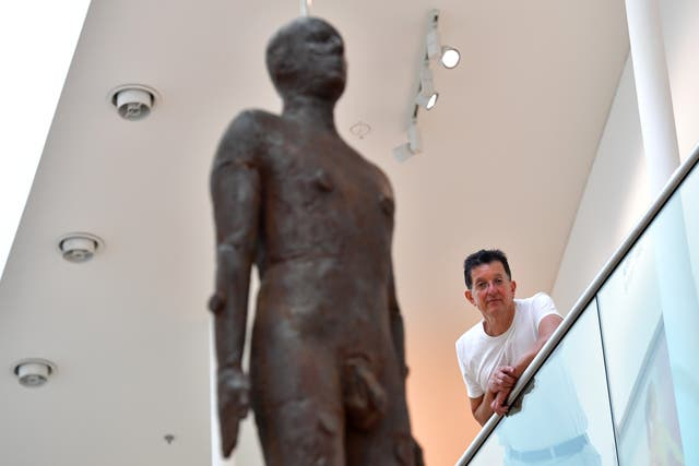 <p>Gormley with his artwork 'Object, 199', a life-size iron sculpture cast from the artist's body and hung from the ceiling of the National Portrait Gallery in 2016</p>