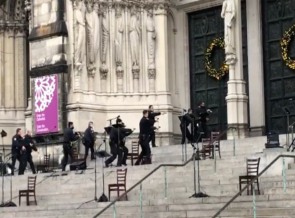 Man shot dead by police after firing semiautomatic handguns at end of Manhattan cathedral Christmas carol concert