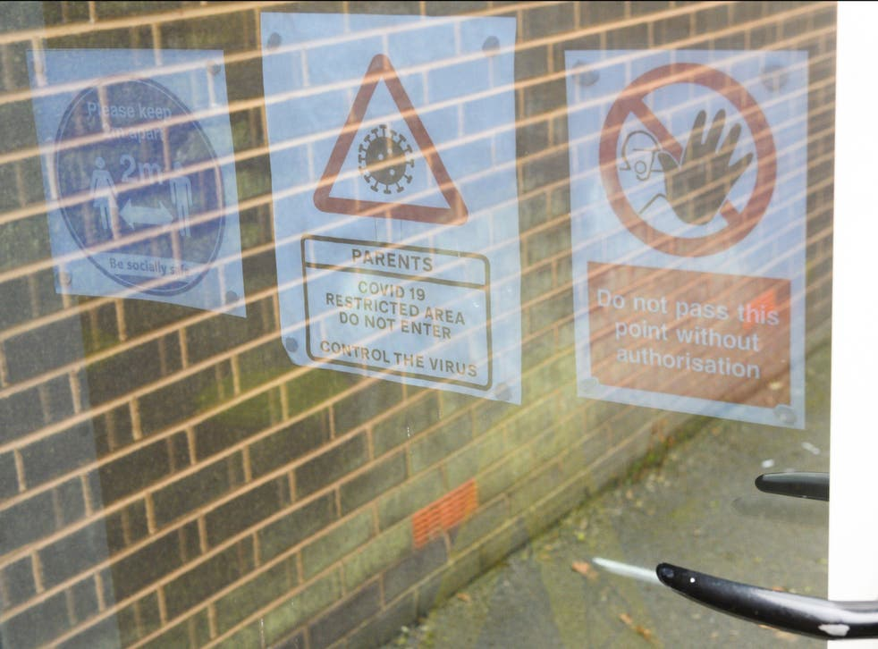 Signage giving Covid-19 related guidance is seen on doors at a primary school