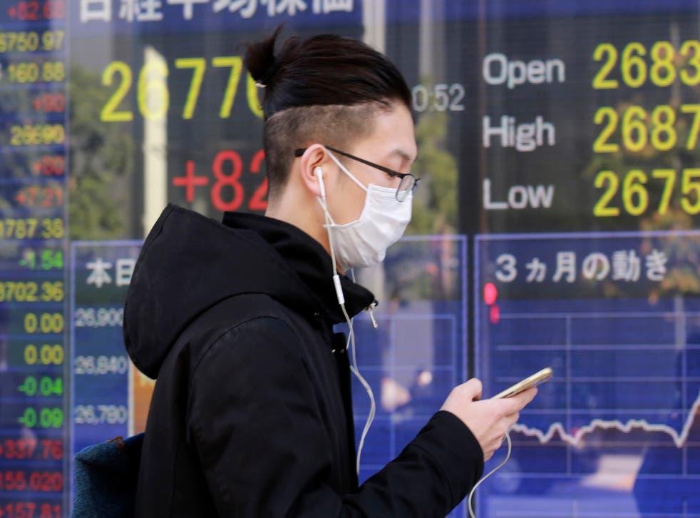 <p>Una persona frente a una cartelera financiera en Tokio el 16 de diciembre del 2020.&nbsp;</p>