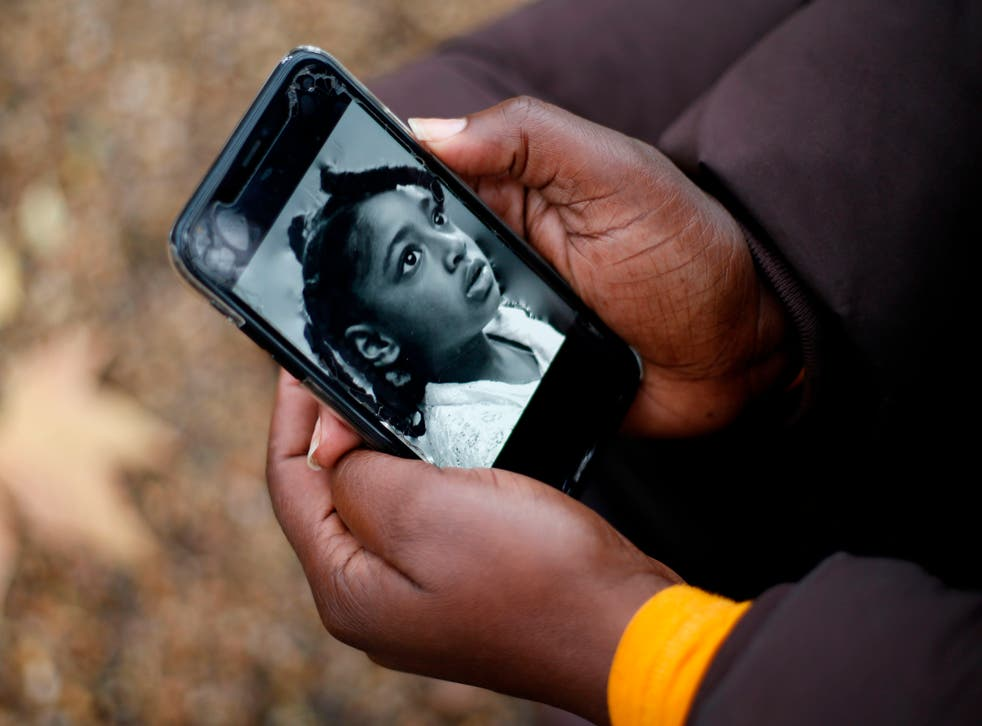 <p>Rosamund Adoo-Kissi-Debrah holds her mobile phone displaying a photograph of her daughter</p>
