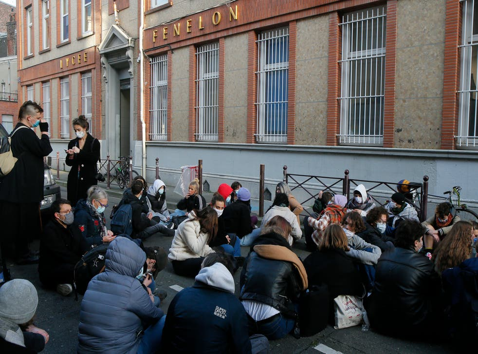 Students stage a sit-in outside the Fenelon High School in Lille, northern France, Friday, 18 December 2020