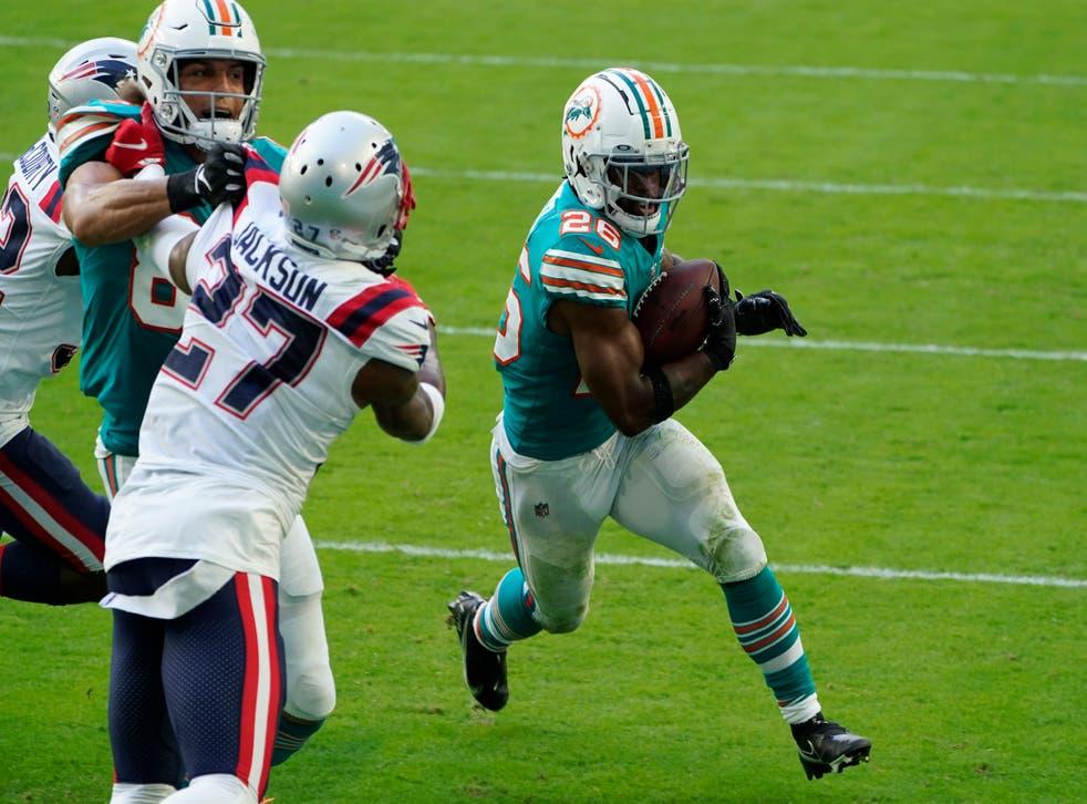 <p>El corredor novato de los Dolphins de Miami Salvon Ahmed corre para la conversión de dos puntos en el encuentro ante los Patriots.</p>