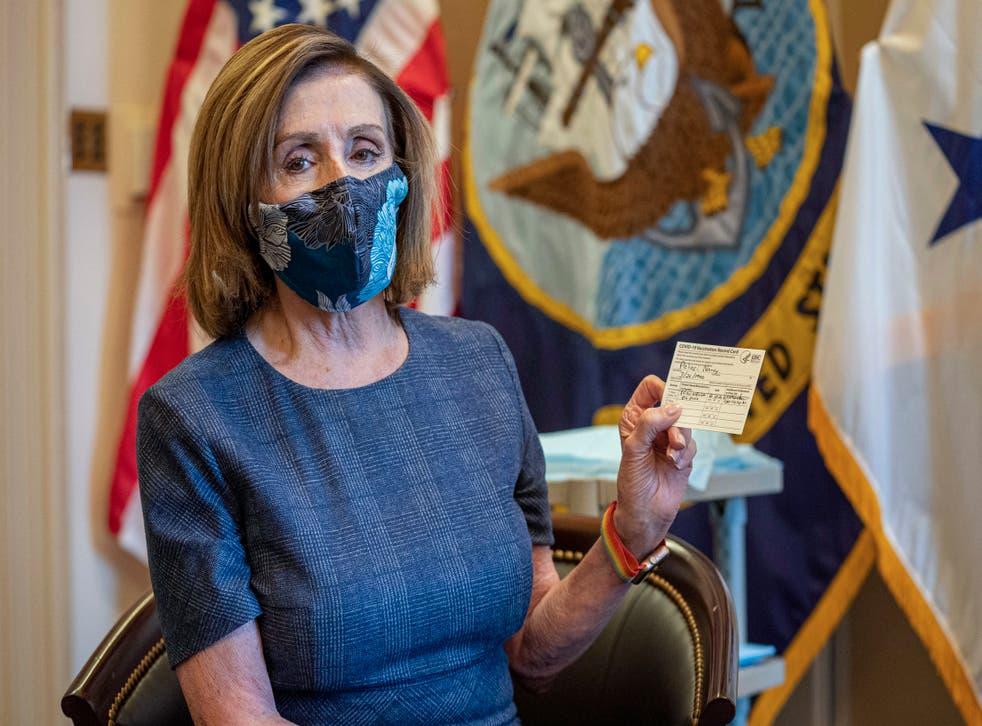 <p>La presidenta de la Cámara de Representantes, la demócrata Nancy Pelosi, sostiene un certificado de vacunación contra el COVID-19.&nbsp;</p>