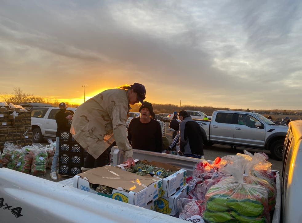 <p>Barbara Doughtie loads boxes of food onto her truck at a mobile food bank in Williston, North Dakota</p>