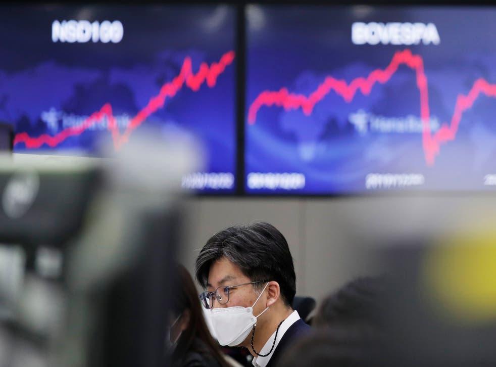 <p>Personas frente a una cartelera financiera en Seúl el 23 de diciembre del 2020. &nbsp;</p>