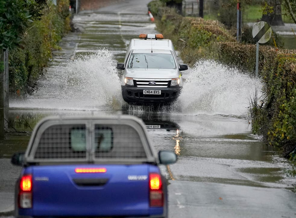 Cars drive on a flooded road as the River Conwy bursts its banks on October 30, 2020 in Llanrwst, Wales. Parts of Wales have been flooded again after heavy rains overnight.