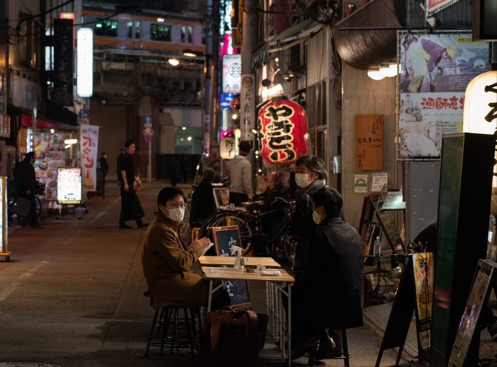 People wearing face masks sit at an outside table of a restaurant on 23 December in Tokyo