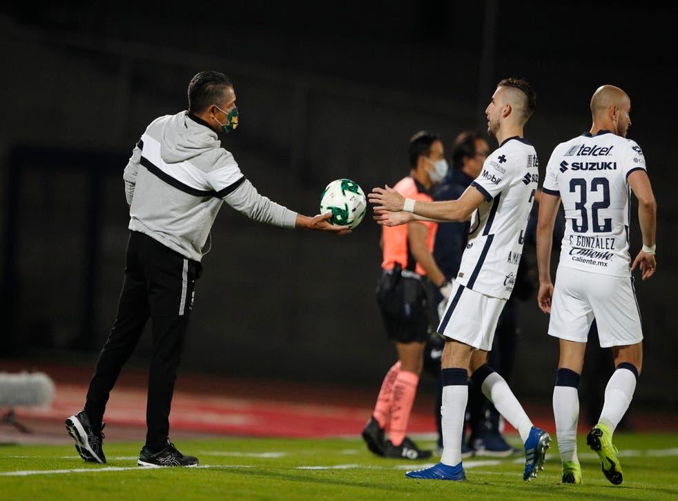 <p>Ignacio Ambriz (izquierda), técnico de León, entrega el balón a Manuel Mayorga, de Pumas, durante el partido de ida de la final de la liga mexicana, el jueves 10 de diciembre de 2020.</p>