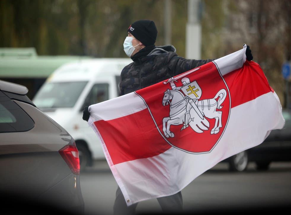 <p>ARCHIVO - En esta fotografía del domingo 22 de noviembre de 2020 un hombre que porta una mascarilla sostiene una bandera bielorrusa durante una manifestación en Minsk, Bielorrusia.&nbsp;</p>