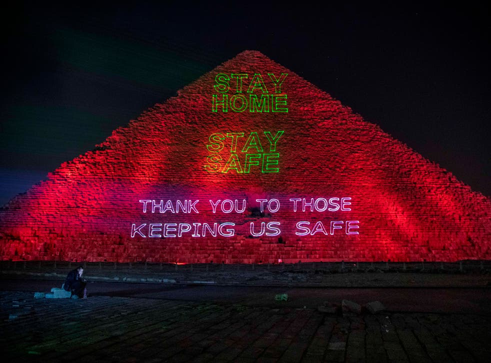 """<p>Un periodista observa su celular mientras autoridades del ministerio de Antigüedades de Egipto encienden sobre la cara de una de las pirámides de Giza un letrero de apoyo a quienes luchan contra la pandemia de coronavirus, el lunes 30 de marzo de 2020. El mensaje en inglés lee """"Quédese en casa y manténgase seguro. Gracias a quienes nos ayudan a mantenernos seguros"""".&nbsp;</p>"""