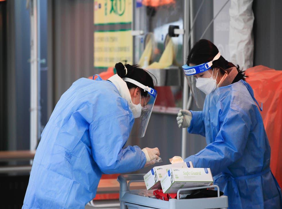 <p>Personal médico con equipo protector contra el coronavirus efectúan pruebas en un lugar en Seúl, Corea del Sur, el domingo 27 de diciembre de 2020.&nbsp;</p>