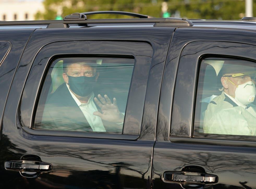 El presidente Trump saluda desde la parte trasera de un automóvil en una caravana fuera del Centro Médico Walter Reed en Bethesda, Maryland, el 4 de octubre de 2020.