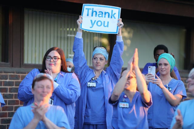 <p>Staff at William Harvey Hospital in Kent join in applause to salute local heroes in April</p>