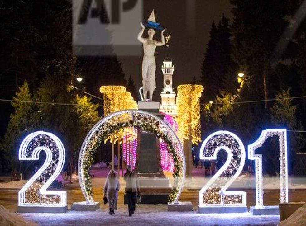 """<p>La gente pasa los números """"2021"""" instalados para celebrar el próximo Año Nuevo en Moscú, Rusia, el martes 29 de diciembre de 2020.</p>"""