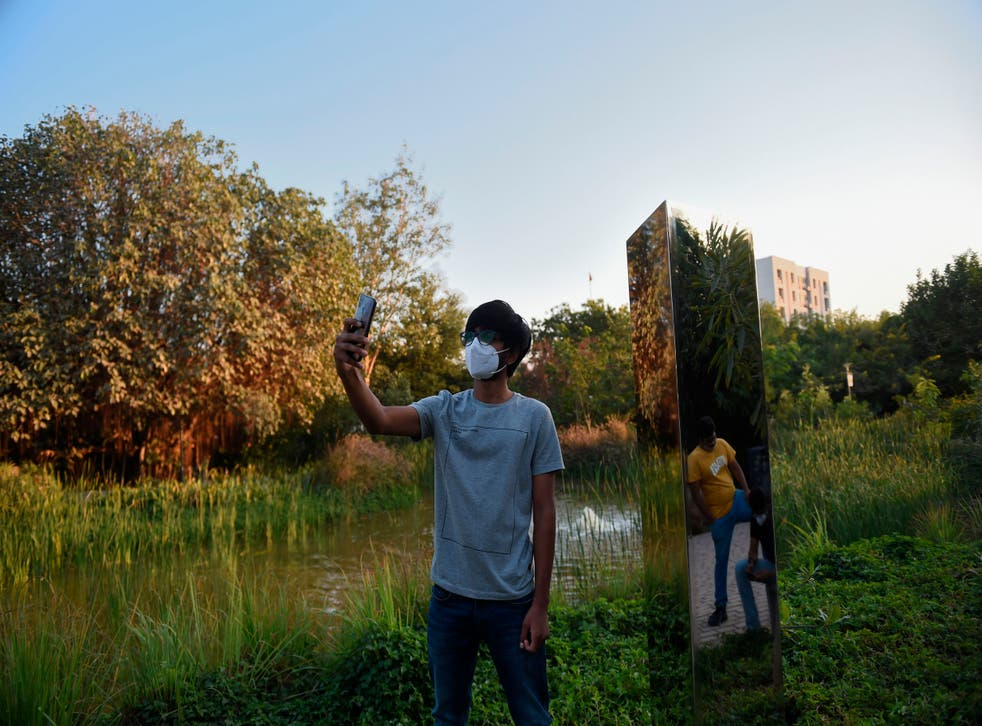 <p>A man takes a selfie with an art installation of a monolith made of steel at Symphony Forest park in Ahmedabad on December 30, 2020</p>