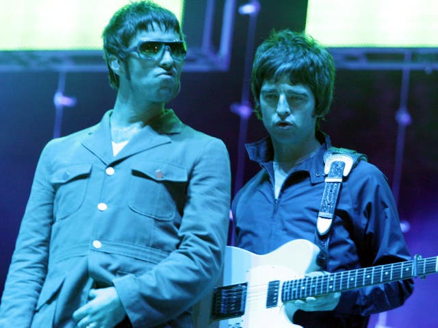 Liam and Noel Gallagher performing together with Oasis in 2005