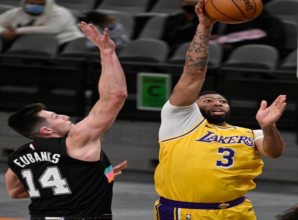 <p>El alero de los Lakers de Los Ángeles Anthony Davis lanza el balón mientras lo defiende Drew Eubanks de los Spurs de San Antonio el viernes 1 de enero del 2021.&nbsp;</p>