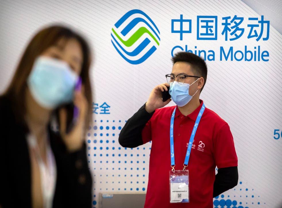 <p>Unas personas cerca de un exhibidor de la empresa china de telecomunicaciones China Mobile en la PT Expo en Beijing, el 14 de octubre de 2020.&nbsp;</p>