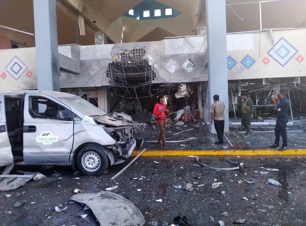 <p>ARCHIVO - En esta fotografía de archivo del miércoles 30 de diciembre de 2020, transeúntes y un soldado se paran cerca de una parte dañada del aeropuerto en la ciudad sureña de Adén después de una explosión. Las autoridades dijeron el domingo 3 de enero de 2021 que el primer vuelo.</p>