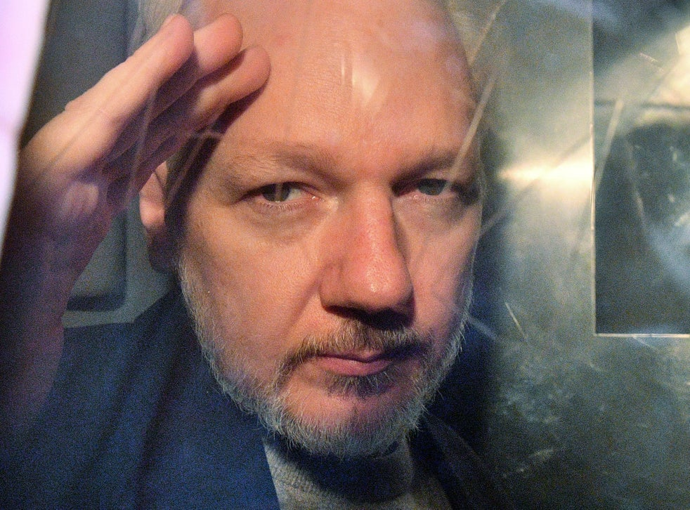 WikiLeaks founder Julian Assange gestures from the window of a prison van as he is driven out of Southwark Crown Court in London on May 1, 2019. Whether he will be extradited to the US will be decided in a UK court on Monday, 4 January, 2020.