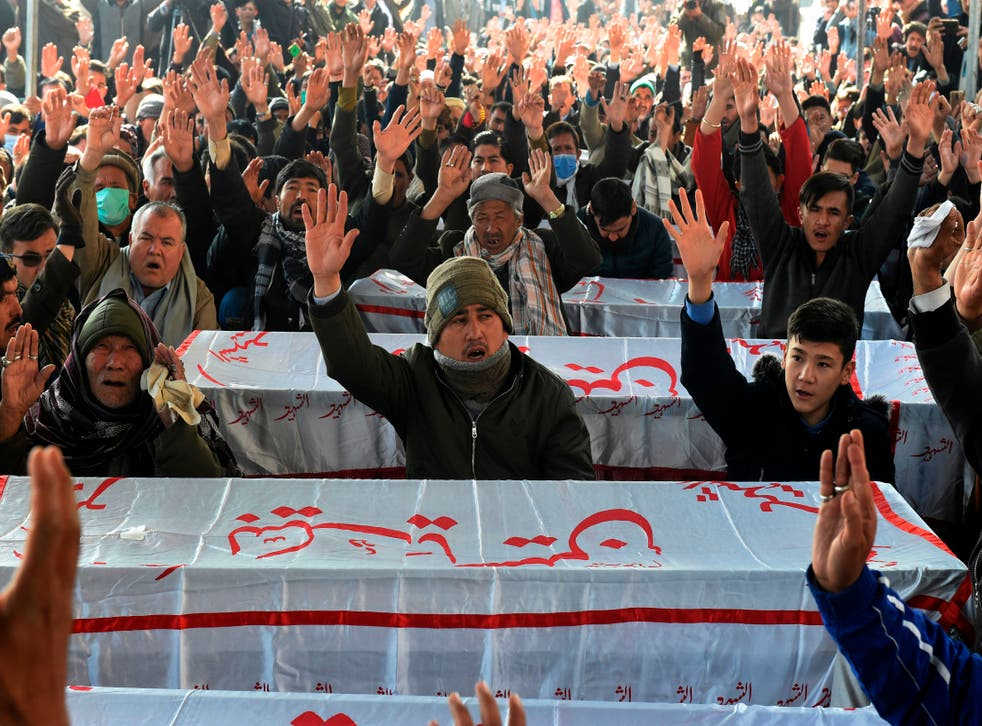 <p>Mourners from Shiite Hazara community chant slogans near the coffins of the miners who were killed in an attack by gunmen in the mountainous Machh area, during a sit-in protest at the eastern bypass, on the outskits of Quetta on January 4, 2021.</p>