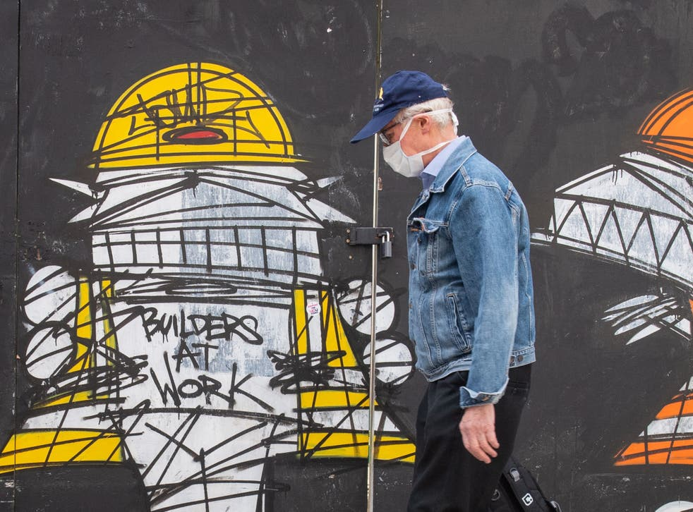 <p>A man wearing a protective face mask walks past a street art mural showing construction workers in central London</p>