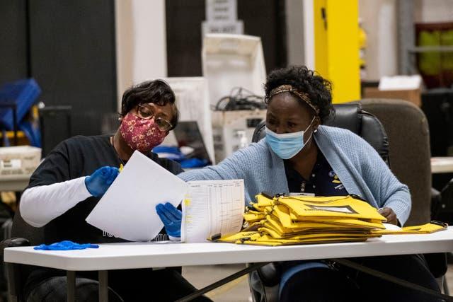 <p>Trabajadores electorales revisan las tarjetas de memoria de las máquinas de votación que almacenan las papeletas, luego de la segunda vuelta de las elecciones al Senado, el martes 5 de enero de 2020, en Atlanta.&nbsp;</p>