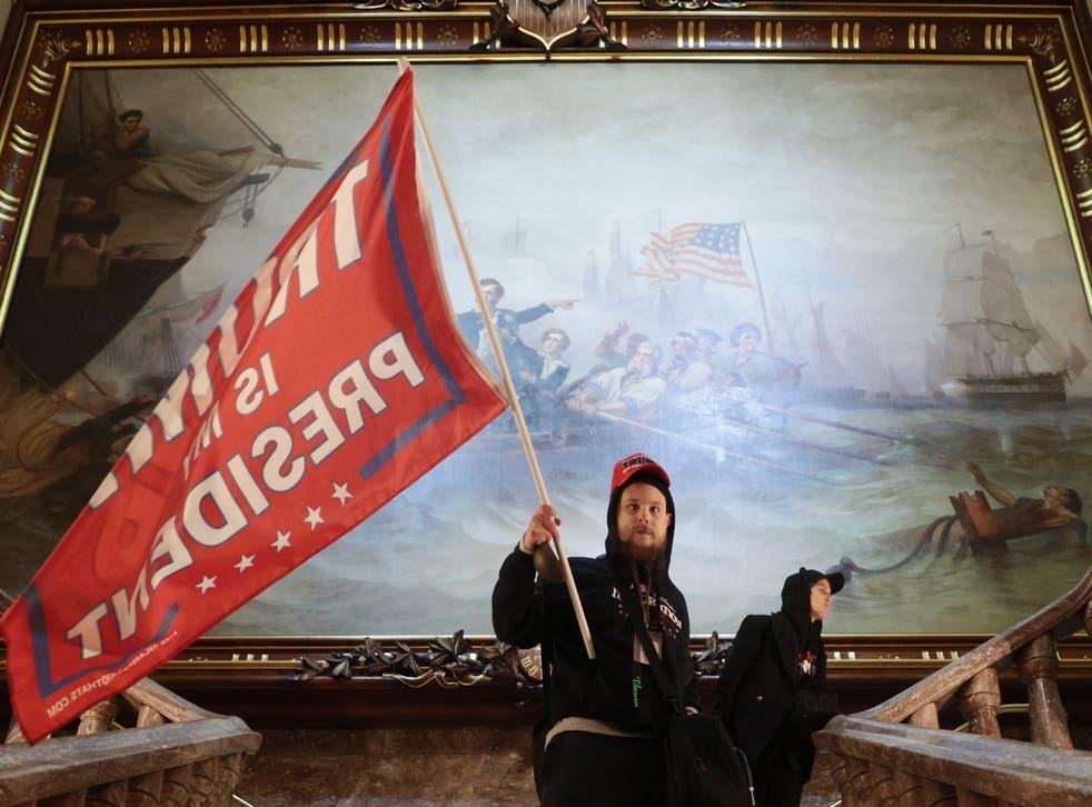 <p>Un manifestante fue fotografiado ondeando una bandera de Trump frente a una enorme obra de arte del siglo XIX dentro del edificio del Capitolio.</p>