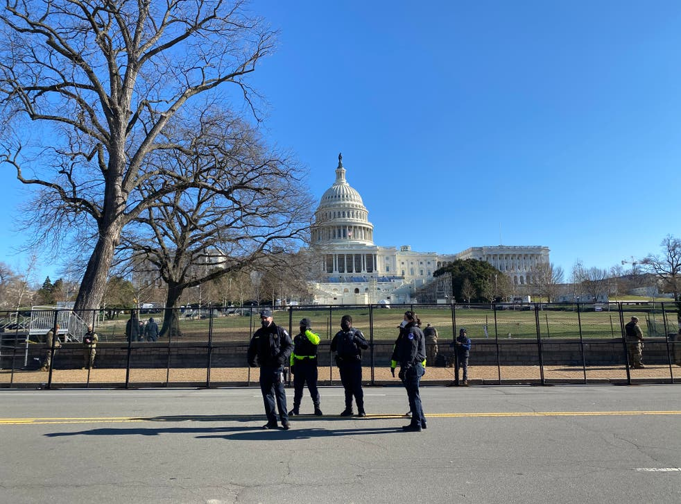 <p>Police stand in front of a newly erected fence outside the US Capitol building a day after it was stormed by a mob of Trump supporters.&nbsp;</p>