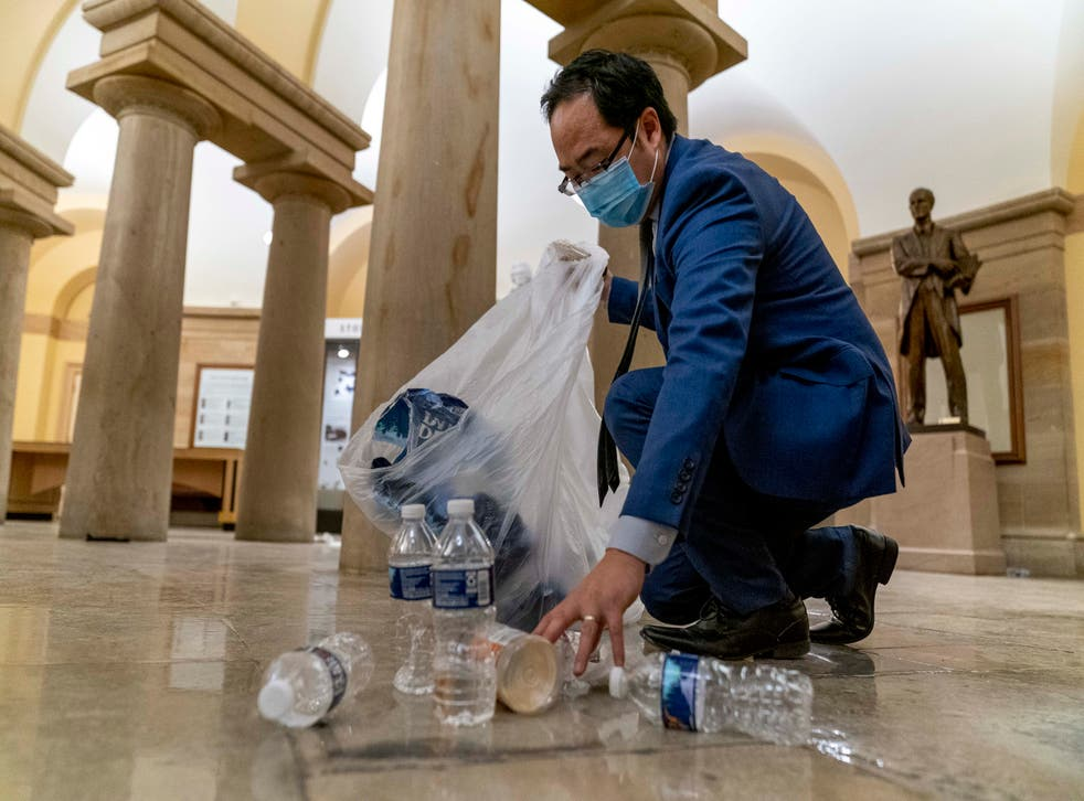 <p>Representative Andy Kim cleans up debris and trash strewn across the floor in the early morning hours of Thursday</p>