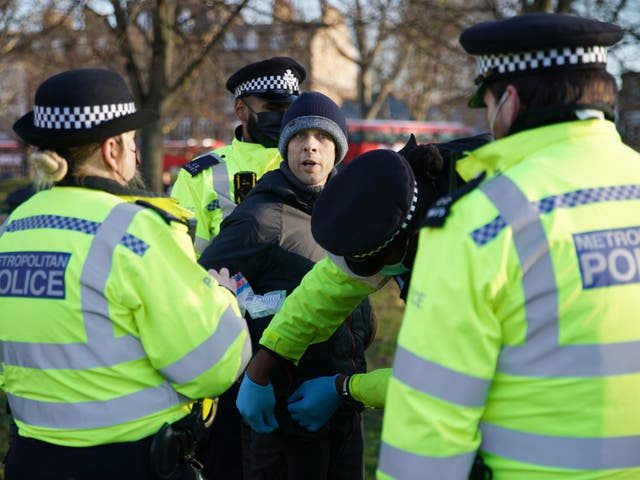 <p>Police detain a man during an anti-lockdown protest in Clapham Common, southwest London</p>